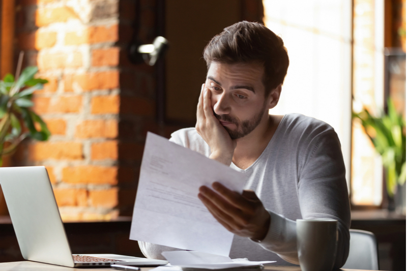 Man looking at sheet with sad expression on face.