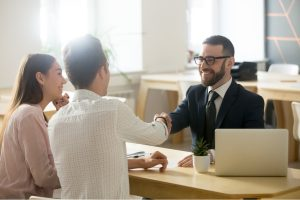 Couple shaking hands with a business professional.