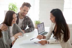 Couple happily working with a business professional.