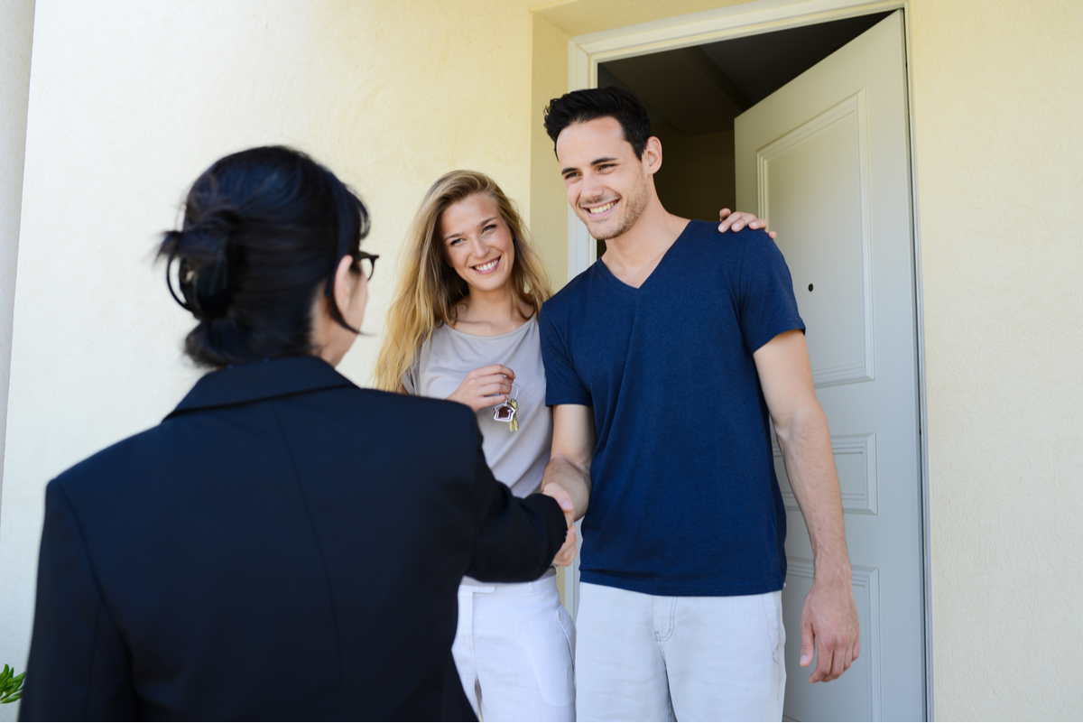 Couple meeting a salesperson at their doorstep.