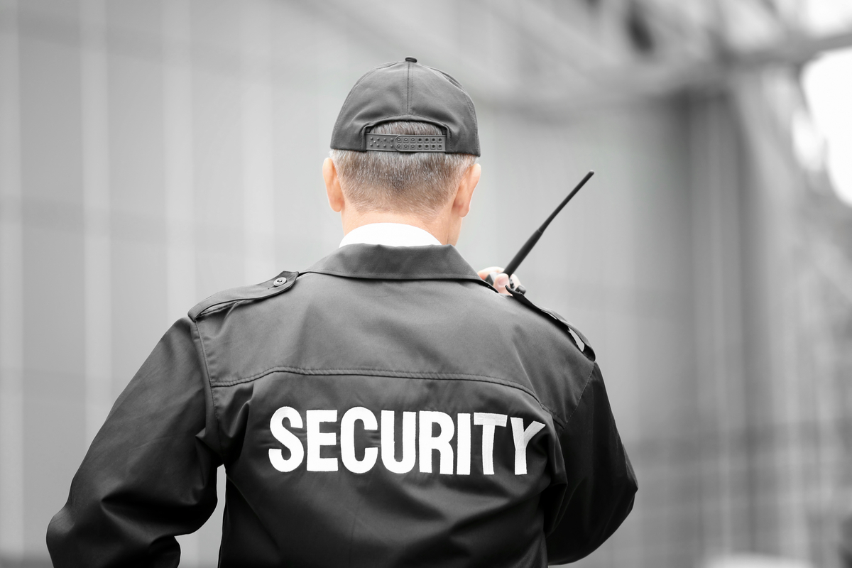 Security officer talking into a communication device.