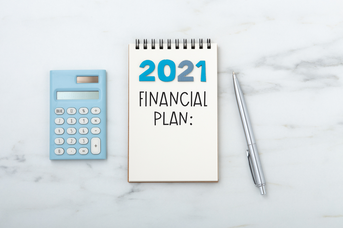"""a notebook with the words """"2021 Financial Plan"""", pen and calculator"""