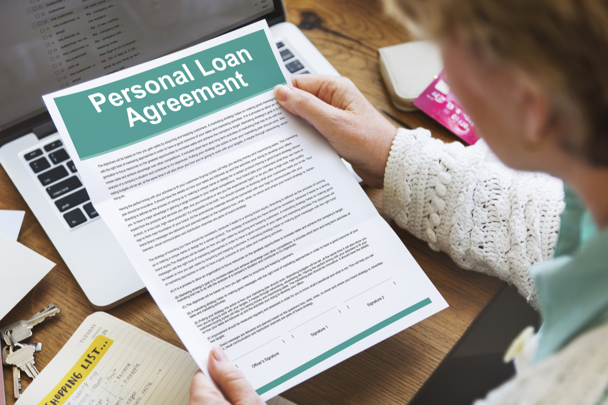 someone holding a personal loan agreement paper.